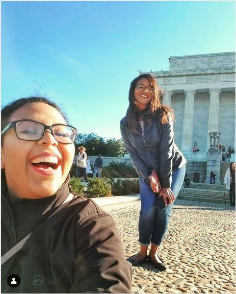 Two people pose joyfully in front of a monument